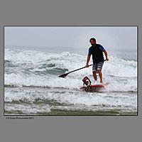 Surfeur avec son chien lors de la compétition européenne de surf canin à Vieux Boucau dans les landes organisée par les Toutous Surfeurs, et la clinique vétérinaire Zatozte, à Bidart (64).Plage des Sablères ( la plage Nord) de Vieux Boucau.