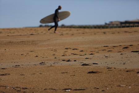 Un Surfeur avec sa planche traverse la plage des Corsaires à Anglet au Pays Basque.  Anglet, Pays Basque, Région Nouvelle-Aquitaine. Aquitaine-Limousin-Poitou-Charentes, France, Europe.
