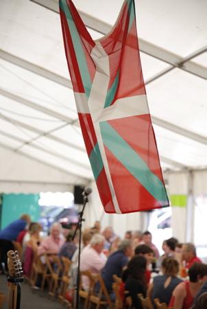 L'Ikurrina, Ikurina, le drapeau du Pays basque lors d'une fête et rencontre basque, ici à Ahetze au Pays basque dans la province du labourd. Aheztarren Eguna, la journée des Aheztar organisée chaque année par l'association et plateforme citoyenne AHH (Ahetzeko Herritarren Hitza)  The Ikurrina, Ikurina, the flag of the Basque Country during a Basque party and meeting, here in Ahetze in the Basque Country in the province of plowing. Aheztarren Eguna, the Aheztar day organized each year by the association and citizen platform AHH (Ahetzeko Herritarren Hitza)  Ahetze, Pays basque, 64 , Nouvelle Aquitaine, Pyrénées Atlantiques, Sud Ouest, South West, France, Europe.New Aquitaine, Basque Country.