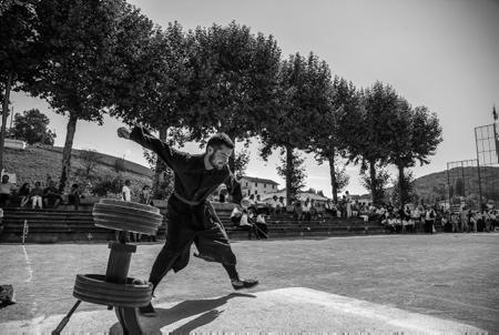 """Lehengo Hazparne du13 aout 2017, partie de rebot avec le curé du village (Anthony Harguindeguy) en soutane, qui fait rebondir la pelote sur le REBOT pour lancer de début de la patie, ici avec les jeunes pilotari de club de pelote basque d'Hasparren NOIZBAIT ( ici Grand Chistera ) en tenue de sport ancienne, reconstitution d'une Fête Populaire Basque en 1900 . C'est sur une idée originale de Jacques COUMET,  en 1971, que naît cette reconstitution de l'ambiance d'une journée en 1900. Hasparren ville du Pays Basque de la province basque du Labourd est en fête et retrouve ses racines pour cette 19ème édition du """"Lehengo Hazparne"""" .Une fête devenue incontournable et sans doute une des plus belles du Pays Basque.  Région Nouvelle-Aquitaine. Aquitaine-Limousin-Poitou-Charentes, France, Europe."""