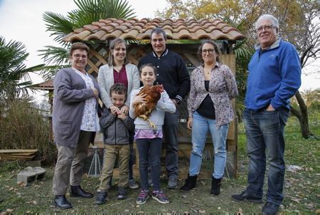 """Le petit IBAN SUZANNE GARAY avec sa poule Cacahouette et sa cousine AMAIA BONNECAZE et leur famille le jeudi 23 novembre  dans le poulailler construit par son papa dans le cadre de l'opération """"Des poules pour réduire les déchets"""" organisé par la commune de Lahonce qui propose à la population une opération innovante pour la réduction des déchets à domicile de leur production de déchets ménagers avec l'adoption de deux poules offertes par la municipalité. Les poules présentent en effet de nombreux avantages. Elles sont friandes de l'ensemble de nos restes alimentaires et donnent en contrepartie de bons œufs frais toute l'année (entre 200 et 250 œufs par an et par poule) Les couples de poules ont pour mission d'ingurgiter environ 300 kilos de déchets par an, un bénéfice environnemental réel.Avec ce nouveau programme, la commune espère réduire encore la partie biodégradable de ses poubelles en proposant à des foyers volontaires d'accueillir deux poules et un poulailler dans leur jardin.Ce dispositif pourra être reconduit jusqu'en 2018 en fonction des demandes.  Lahonce, Pays basque, Nouvelle Aquitaine, Pyrénées-Atlantiques, Europe, France."""