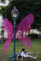 Deux jeunes amoureux sur un banc avec une decoration au jardin public de papillons geant lors du Festival des Arts de la rue de Biarritz organise par l association Biarritz Evenement edition 2017.