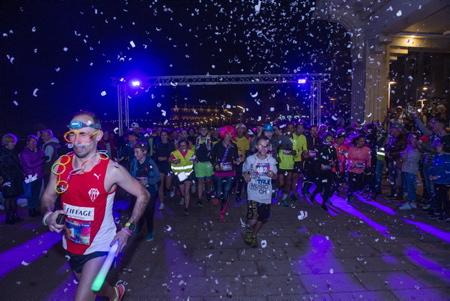 La course des illumines a Biarritz au Pays Basque organise sur une distance de 5 Kms avec une ambiance phosphorescente lors de l evenement Biarritz en lumieres, les coureurs, marcheurs et familles equipes de materiel fluo et fluorescents partent de la grande plage.  Région Nouvelle-Aquitaine. Pays Basque, Pyrenees-Atlantiques,  Aquitaine-Limousin-Poitou-Charentes, France, Europe.