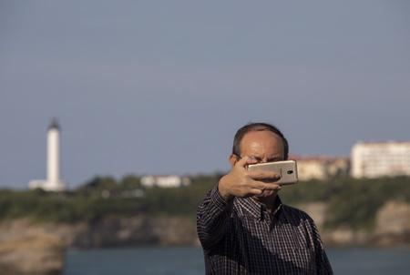 Auto-Portrait, selfie avec la phare de Biarritz en arrière plan lors d'un séminaire à Biarritz sur la place bellevue. Tourisme d'affaires, sémininaire de travail et incentive au Pays basque, ici à Biarritz.  Biarritz, Pays Basque, Nouvelle Aquitaine, Pyrénées Atlantiques, Sud Ouest, France, Europe.