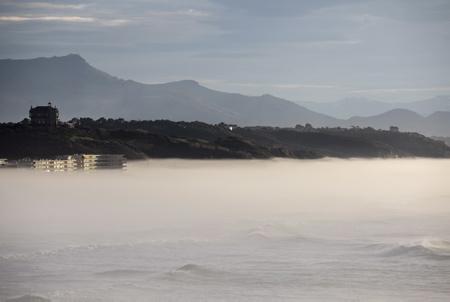 Biarritz le 15 fevrier 2018, sur la plage de la côte des basque l'océan avec la montagne de la rhune avec une température de 20 degrés après des mois de pluies sur le pays basque nord. La résidence de la milady est prise d'assaut par l'arrivée d'une entrée maritime ( Brouillarta ) qui découpe le panorama en deux.  Biarritz, Pays Basque Pyrenees-Atlantiques, Region Nouvelle-Aquitaine.France, Europe.