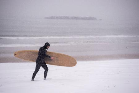 Un surfeur sur la Grande plage de Biarritz avec sa planche au Pays Basque sous la neige le 28 fevrier 2018.  Biarritz, Pays Basque, Region Nouvelle-Aquitaine, Pyrenees-Atlantiques France, Europe.