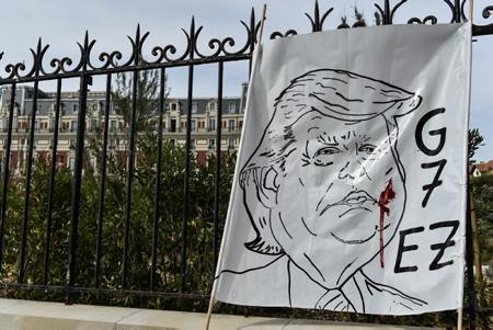 """Portrait et caricature de Donald Trump accroché à la grille de l'Hôtel du Palais de Biarritz lors de la grande manifestation anti G7 le 13 juillet 2019 à Biarritz, à l'Appel de la plate-forme « G7 EZ » pour dire non au G7 qui doit se tenir du 24 au 26 août à Biarritz au Pays Basque. Ils étaient environ un millier d'opposants dans la station balnéaire.  Portrait and cartoon of Donald Trump hanging on the grid of the Hotel du Palais in Biarritz during the great anti-G7 demonstration on July 13, 2019 in Biarritz, at the Appeal of the platform """"G7 EZ"""" to say no to the G7 to be held from 24 to 26 August in Biarritz, Basque Country. There were about a thousand opponents in the resort.   Biarritz, Pays basque, 64 , Nouvelle Aquitaine, Pyrénées Atlantiques, Sud Ouest, France, Europe. New Aquitaine, Basque Country."""