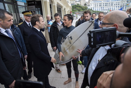 Emmanuel Macron en visite de repérage à Biarritz au Pays Basque dans le cadre du futur G7 de cet été 2019 rencontre un surfeur qui sort de l'eau.
