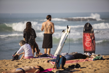 Un homme avec un squelette tatoué dans le dos et sa planche de surf LOVE à la Grande plage de Biarritz le 27 fevrier 2019 27° les locaux et touristes prennent d assaut la grande plage de Biarritz au pays basque.  Pays basque, Nouvelle Aquitaine, Pyrénées-Atlantiques, Pays Basque, Europe, France.