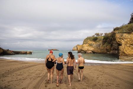 """Betty """"ourse blanche"""" de 92 ans et le docteur Guillaume Barucq au centre de l'image, lors de leur baignade dans l'océan à la plage du port vieux de Biarritz le 10 novembre 2020. Confinement baigneur en colere, des ainés entre autres, des Ours Blancs une association mythique de Biarritz au Pays basque, interdits de baignade malgrès un avis médical en leur possession, BETTY agée de 92 ans, commence à faire parler d'elle avec cette """"altercation"""" avec la police, des slogans comme LAISSZ NAGER BETTY et LET BETTY SWIM et DU SPORT SUR ORDONNANCE  VAUT MIEUX QUE DES MEDICAMENTS apparaissent sur le fil sur les reseaux sociaux. Les Ours blancs sont à l'eau l'année,médiatisés surtout pour leur traditionnel bain de Noël , plage du Port-Vieux, leur règle d'or pour l'hiver quand l'eau est très très froide est de se baigner autant de temps qu'il y a de degrés dans l'eau mais pas plus.   Betty """"white bear"""" of 92 years and doctor Guillaume Barucq during their bathing trip in the ocean at the beach of the old port of Biarritz on November 10, 2020. Containment of an angry bather, elders among others, White Bears a mythical association of Biarritz in the Basque Country, banned from bathing despite a medical opinion in their possession, BETTY aged 92, begins to make talk about her with this """"altercation"""" with the police, slogans like LET BETTY and LET BETTY NAGER SWIM and PRESCRIPTION SPORT IS BETTER THAN DRUGS appear on social media feed. The Polar Bears are in the water year round, especially publicized for their traditional Christmas swim, Port-Vieux beach, their golden rule for winter when the water is very very cold is to bathe as many time that there are degrees in the water but not more.  Biarritz, Pays basque, 64 , Nouvelle Aquitaine, Pyrénées Atlantiques, Sud Ouest, France, Europe, New Aquitaine, Basque Country."""
