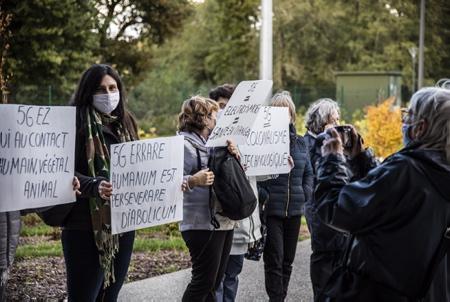 """Militante manifestante ANTI 5G avec une pancarte en langue Latine """"L'Erreur est humaine, persister est diabolique"""". Rassemblement et manifestants des associations Ahh Ahetzeko Herritarren Hitza, Askilinky, ACE Hendaye et Linkyrik Ez, avec banderoles et pancartes anti 5G pour appuyer la demande d'un moratoire à l'échelle de l'Aglomération Pays Basque. Eneko Aldana, le plus jeune Maire de la côte basque et du Pays basque, Maire de la ville de Ciboure et Président du """" Pôle Sud Pays Basque """" de la Communauté Pays Basque à réunit les élus(e) délégué(es) à la Communauté d'Agglomération Sud Pays basque,  le mercredi 14 octobre à Ciboure pour traiter de la 5G, avant de faire une proposition de moratoire à la CAPB.  ANTI 5G demonstrator activist with a Latin language sign """"Error is human, to persist is diabolical"""". Rally and demonstrators from Ahh Ahetzeko Herritarren Hitza, Askilinky, ACE Hendaye and Linkyrik Ez associations, with anti 5G banners and placards to support the demand for a moratorium on the scale of the Basque Country. Eneko Aldana, the youngest Mayor of the Basque coast and the Basque Country, Mayor of the city of Ciboure and President of the """"South Pole Basque Country"""" of the Basque Country Community, brings together the elected representatives of the Community of Agglomeration South Basque Country, Wednesday October 14 in Ciboure to deal with 5G, before making a moratorium proposal to the CAPB.  Ciboure, Pays Basque, Nouvelle Aquitaine, New Aquitaine, Basque Country, Pyrénées Atlantiques, Sud Ouest, France, Europe."""