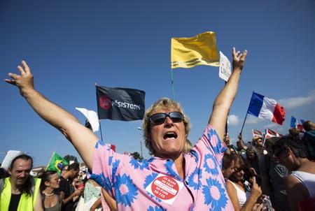 Un manifestant anti PASS SANITAIRE avec une chemise à fleur rose et bleu, chemise Hawaienne  lève les bras en l'air , Rencontre entre Basque, Espagnol et Français sur le pont Saint Jacques lors de la manifestation transfrontalière entre Hendaye, Pays basque français et Irun au Pays basque espagnol contre le PASS SANITAIRE le 4 septembre 2021, plus de 2000 manifestants entre Basques espagnol, espagnol et français, ( plus de Français ) se sont retouvés après leur départ de leur mairie respective sur le pont Saint-Jacques, points de passage transfrontalier entre Hendaye et Irun.  An anti PASS SANITAIRE protester with a pink and blue flowered shirt, Hawaiian shirt raises his arms in the air, Meeting between Basque, Spanish and French on the Saint Jacques bridge during the cross-border demonstration between Hendaye, French Basque Country and Irun in Spanish Basque Country against the SANITARY PASS On September 4, 2021, more than 2000 demonstrators between Spanish, Spanish and French Basques (more French) met after their departure from their respective town hall on the Saint-Jacques bridge, cross-border crossing points between Hendaye and Irun.  Hendaye, Irun, Pays basque, Côte basque, 64 , Nouvelle Aquitaine, Pyrénées Atlantiques, Sud Ouest, France, Europe. New Aquitaine, Basque Country.