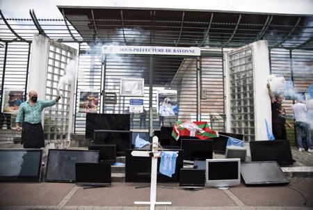 Le collectif les cafetiers en colère (Kasu Kasu ostatalariak kexu ) EN BASQUE, ici en action symbolique vers et devant devant la sous-préfecture de Bayonne au Pays basque le  vendredi 11 juin 2021, avec le dépot de vieux écrans de télévision cathodiques .Ceci en réaction à l'arrêté préfectoral qui interdit la diffusion sur écran du match de rugby de barrage entre le Biarritz Olympique Pays basque et l'Aviron Bayonnais du 12 juin 2021. L'Umih (Union des métiers et des industries de l'hôtellerie) lui  a affiché son mécontentement dans un communiqué.   The collective angry cafetiers (Kasu Kasu ostatalariak kexu) IN BASQUE, here in symbolic action towards and in front of the sub-prefecture of Bayonne in the Basque Country on Friday June 11, 2021, with the deposit of old cathode-ray television screens. reaction to the prefectural decree which prohibits the broadcast on screen of the play-off rugby match between the Biarritz Olympique Pays Basque and the Aviron Bayonnais of June 12, 2021. The Umih (Union of trades and hospitality industries) him posted his dissatisfaction in a statement.  Bayonne, Pays basque, Nouvelle-Aquitaine, New-Aquitaine, Pyrénées-Atlantiques, Pays Basque, Europe, France.