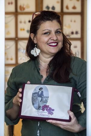 """Hélène Demé Elzévir, de son nom de créatrice Hortense de Biarritz pose avec le portrait de sa grand mère (qui etait couturière) imprimé sur une pochette de sa fabrication. Hortense est à l'initiative de la création d'une technique spécifique de solidification des fleurs. Les bijoux de """"Hortense de Biarritz"""" en fleurs solidifiées sont montés sur argent, des pièces uniques de bijoux solides qui tiennent des années. La pandémie du coronavirus étant passée par là, Hélène Demé Elzévir qui est également comédienne depuis 2016 avec à son actif, l'écriture spectacle PILE POIL qui l'a révélé et fait un tabac a perdus pas moins de 45 dates de spectacle. Un vrai cauchemar pour elle, mais une raison de plus de ne rien lâcher et de produire un peu plus de bijoux et d'objets en attendant le retour des beaux jours et celui de la scène. Soutenez là ! et """"Offrez des fleurs qui ne fanent jamais !"""" c'est ici avec la possibilité de commande en ligne : www.hortensedebiarritz.com  Hélène Demé Elzévir, her designer name Hortense de Biarritz, poses with the portrait of her grandmother (who was a seamstress) printed on a pocket of her own making. Hortense initiated the creation of a specific technique for solidifying flowers. The jewelry of """"Hortense de Biarritz"""" in solidified flowers are mounted on silver, unique pieces of solid jewelry that last for years. The coronavirus pandemic having been there, Hélène Demé Elzévir who has also been an actress since 2016 with to her credit, the writing show PILE POIL which revealed it and made a splash lost no less than 45 show dates. A real nightmare for her, but one more reason not to give up and to produce a little more jewelry and objects while waiting for the return of the beautiful days and that of the scene. Support there! and """"Give flowers that never wither!"""" it is here with the possibility of ordering online: www.hortensedebiarritz.com  Arbonne, Pays basque, 64 , Nouvelle Aquitaine, Pyrénées Atlanti"""