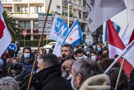 Clément Pottier, professeur adhérent de la FSU-64, en intervention lors du mouvement de grève de l'intersyndicale de l'Education Nationale, mardi 26 janvier 2021, devant la sous-préfecture de Bayonne au Pays basque. Des enseignants dans la rue à Bayonne lors d'une manifestation intersyndicale à l'appel de l'UNSA, la CGT, FO, la FSU. 240 personnes sont parties de la sous préfecture pour l'antenne de l'inspection d'académie (école des arènes) puis la mairie de Bayonne. Trois thèmes de mobilisation : les salaires des profs, les suppressions de postes et les règles sanitaires dans les établissements scolaires.  Clément Pottier, professor member of the FSU-64, in intervention during the strike movement of the intersyndicale de l'Education Nationale, Tuesday January 26, 2021, in front of the sub-prefecture of Bayonne in the Basque Country. Teachers in the street in Bayonne during an inter-union demonstration called for by the UNSA, the CGT, FO, the FSU. 240 people left the sub-prefecture for the office of the inspectorate of the academy (arena school) then the town hall of Bayonne. Three themes of mobilization: teachers' salaries, job cuts and health rules in schools.  Bayonne, Pays basque, 64 , Nouvelle Aquitaine, Pyrénées Atlantiques, Sud Ouest, France, Europe. New Aquitaine, Basque Country.